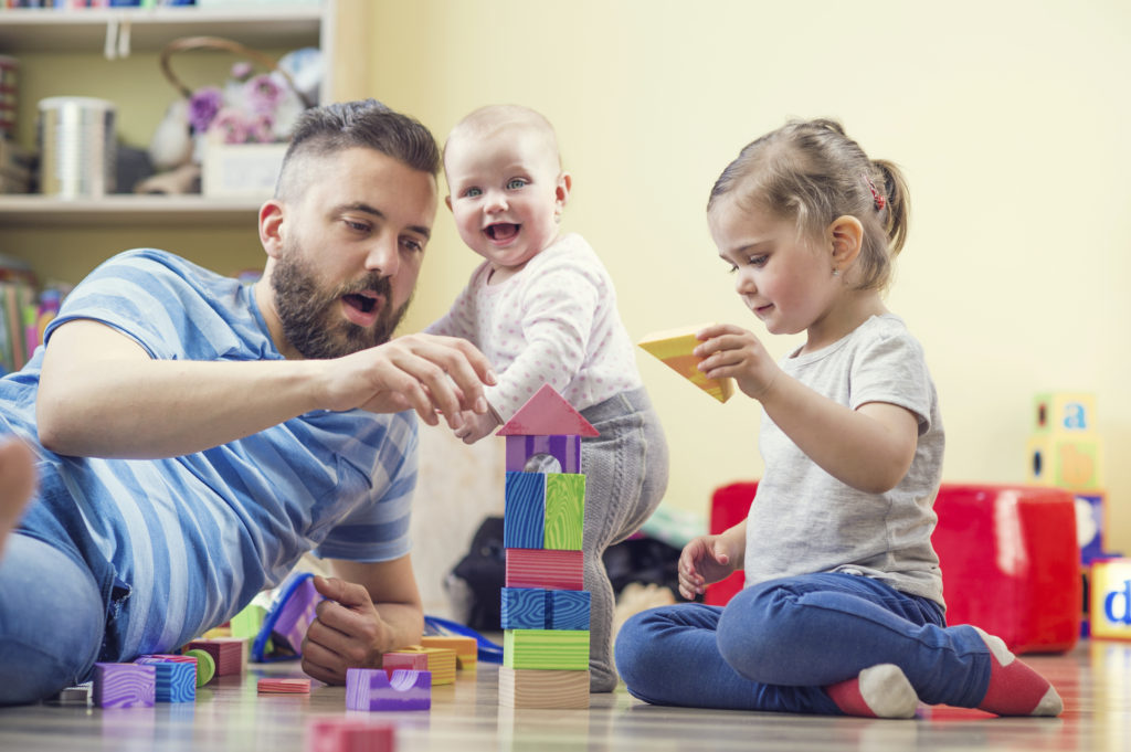 Young father playing with his daughters